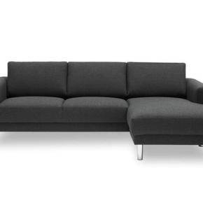 Mørkegrå chaiselongsofa med et tidsløst design. Mål 231cm x 140 cm x 81 cm,   Sofaens puder og sæder er udført i formstabilt og hygiejnisk polyether-skum, mens benene fremstår i blankt krom.  Ny pris 5599,- købt i Idemøbler for 2 år siden.