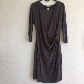 Grå kjole fra H&M, med dyb V udskæring i en wrapstyle. Brugt få gange.