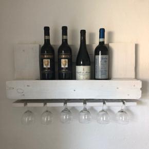Flot hvidbejdset retro vinhylde - håndlavet af træ fra euro palle.  Mål: b:67cm, h:33cm, d:14cm  Skruer + plugs til ophæng medfølger.  Kan sendes med GLS for 75kr.  (glas og flasker medfølger ikke)