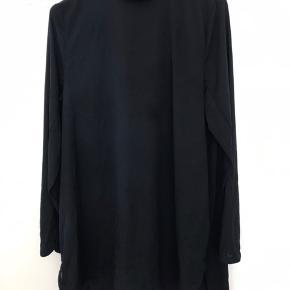 I 100% silke. Den måler 81 cm i længden.