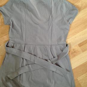 Varetype: Sød og feminin bluse Farve: Grå Prisen angivet er inklusiv forsendelse.  Sød og feminin bluse med bindebånd på ryggen samt søde detaljer. Str. XL. Fremstår som ny.  KOM MED ET BUD!