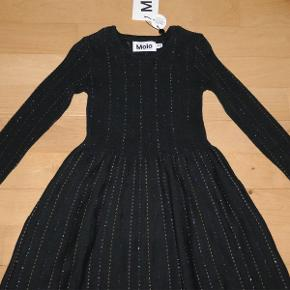 Varetype: *NY* strik kjole Bemærk: størrelsen hedder 98/104 - den er lille i størrelsen (smal)! Farve: sort med glimmer-striber Oprindelig købspris: 499 kr.  Flot kjole fra Molo, som aldrig har været brugt - mærket sidder stadig i.  Bud fra 200 kr. pp.  Medmindre andet aftales, sender jeg med DAO til DK adresser.  Jeg bytter ikke, men handler gerne via Mobilepay :-)