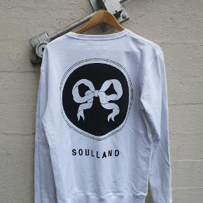 Hvid Soulland sweatshirt med deres ribbon logo på bryst og ryg. Er krid-hvid da den har været brugt uendelig lidt. Jeg er 185cm og den passer mig perfekt.