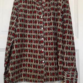 Fin skjorte i 75% bomuld og 25% silke. Brugt , men uden huller, pletter, fnuller eller lign. Har klippet str ud, men husker den som en str. 38. Jeg er selv en 36-38 og passer den. Tjek evt mål:  Brystmål: 52 cm på tværs fra armhule til armhule, dvs 104 cm i omkreds. Længde: 68 cm fra nakken og ned. Søgeord: skjorte shirt bluse mønstret mønster paisley silk cotton silke rød grøn sort beige langærmet kinakrave Kina krave