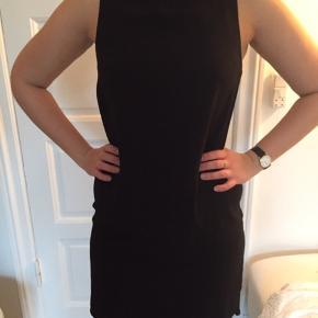Sort klassisk kjole. Længere bag på end foran. Rund hals. Lynlås bag på.