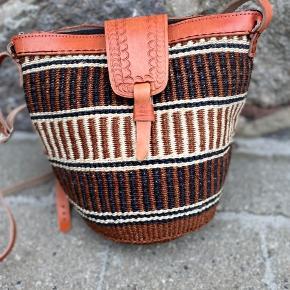 Smuk, håndlavet sisaltaske med detaljer af ægte læder. Læderremmen kan justeres til den ønskede længde. Åbningen på tasken er ca. 29 cm. Den er foret indvendigt og der er lynlås i toppen.   Se flere tasker på min profil i forskellige designs og størrelse.   Taskerne er købt på lokale markeder i Kenya.  Varen kan sendes med DAO eller afhentes efter aftale.   # Crossbody taske, Afrika, Kenya, sisal, unik