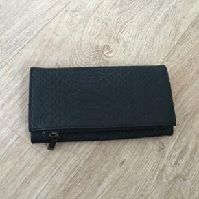 Pung i matte sort med slangskind mønstre - helt ny og aldrig brugt, med masse plads til det hele - 16 kort, 2 lynlås rum og endnu flere plads.   100,- pp.