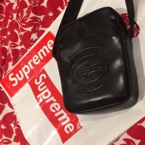Jeg sælger denne super fine Supreme x Lacoste Shoulder Bag Black i en super fin stand. Den er i rigtig lækker kvalitet og har rigtig meget plads så du nemt kan have en masse ting med på farten. Både pose og sticker følger med. Den er købt i Roundtwo i New York 🔥 nogle små ridser nogle steder   Mp 800 Bin 900 Byd endelig!