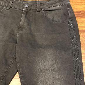Varetype: Jeans Størrelse: 28 Farve: Sort Oprindelig købspris: 899 kr.  Fede jeans med sorte sten ned langs siden Livvidde 39 cm  Bytter ikke