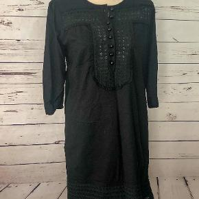 This fully-lined, eyelet fabric dress has rounded buttons down the front.  100% cotton.  Machine wash warm.