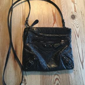 Fin sort crossover taske. den ligner meget en Balenciaga. Den måler 19x16 cm og hanken er ca. 125 cm. Den har 3 rum. Bytter ikke. sælges for 200 kr. Se også mine andre annoncer!!!
