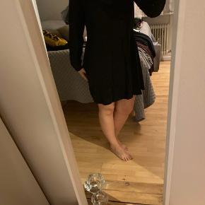 Sort kjole med pliche i bunden bagpå og lidt åben i nakken