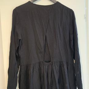 Fin bluse med peplum effekt og lange ærmer. Åbning på ryggen