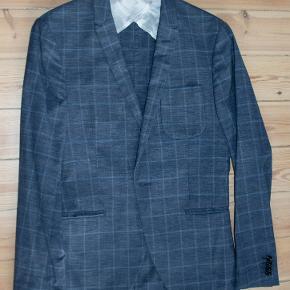 Flot blazer i 100 % uld. Let sommermodel. Støvet blå (nærmest jeansfarvet) med lysere blå tern. Style Evert 10BZ. Meget fin stand. #30dayssellout