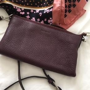 Smuk lille taske med rum til kreditkort. Kan bruges som Clutch eller cross- body med lang rem. Aldrig brugt. Er som ny