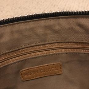 Læder skuldertaske fra det norske mærke Hippi Grace. Har flettet skulderrem, som også går igen foran på tasken. 27x19.