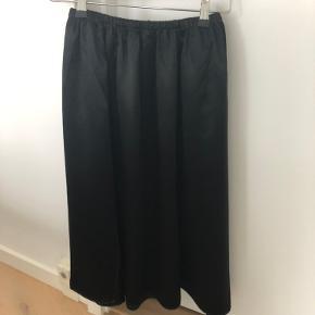 Nederdel med lille slids i den ene side bag til og med lommer