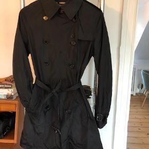 Varetype: Trenchcoat Farve: Sort Oprindelig købspris: 3500 kr.  Rigtig fin, klassisk trenchcoat fra Burberry i størrelse UK 8/34-36. Den er let foret og en lille pouch til at pakke jakken ned i medfølger.  Nypris 3500,-.