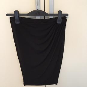 Klassisk flot sort tætsiddende nederdel fra Zara med drapering i siden. I rigtig fin stand.