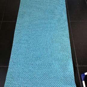 Pappelina tæppe i vævet plast. Farven er mint/turkis. Mål: 157 cm x 70 cm. Nypris 899 kr. Kan vaskes ved 30 grader i vaskemaskine.