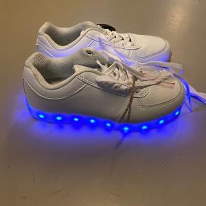 Sko med lys såler som kan blinke og indstilles til forskellige farver. Kan tændes og slukkes og lades op. Har kun været brugt en gang.