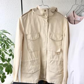 Beige jakke fra Massimo Dutti med snøring i livet. Knapper i guldfarve. Hætte. Let vandafvisende. Størrelse S😊