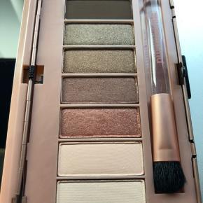 """""""Secret Crush"""" Eyeshadow Palette fra PÜR Minerals består af otte nuancer med en række matte, satin og glitrende farver. Med silkebløde og lette teksturer, og øjenskyggerne er blandbare og bygbare, så du kan skabe professionelle resultater hver gang. Glider ubesværet på lågene, og du kan eksperimentere ved at påføre over det hele for en smokey effekt eller fremhæve konturerer for et look så dramatisk eller naturligt som ønsket. Leveres i et chik etui med en praktisk applikationsbørste og spejl, så øjenskyggerne er ideelle til brug på farten. E.N.  Nuancerne omfatter: Whisper, Lust, Passion, Muse, Infatuation, Admirer, Rendezvou, Rumor.  PÜR Minerals tester IKKE sine produkter på dyr.  OBS: der er en revne i spejlet, men ellers er det ubrugt"""
