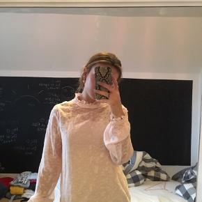 Super fin skjorte med flæsedetaljer fra VILA i sart lyserød. Aldrig brugt. Har en indbygget undertrøje, der dog nemt kan fjernes, hvis det er ønsket.