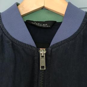 Fin overgangs/indendørs jakke fra Zara man i str.m. Mørkeblå med lyseblå ribkrave og grå ribkant forneden og på ærmer. Lynlås foran og to lynlåslommer i siderne. Rigtig fin stand.