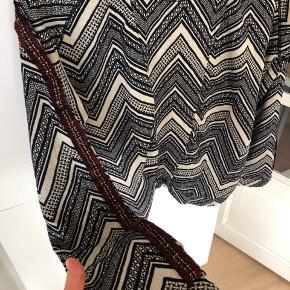 Fin bluse i lys beige med mørkeblå striber. Fine detaljer på ærmerne i Bordeaux og guldfarve.