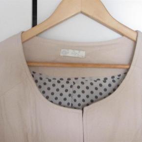 Fin jakke/blazer, der kan lukkes med en enkelt hægte. Ren bomuld, sødt, prikket for, let vatteret. Passer til det meste. Kun brugt 2-3 gange.  Bryst: ca. 2 x 60 cm, længde fra skulder ca. 71 cm.   JEG BETALER FORSENDELSEN!  Fin, quiltet jakke Farve: Lys sand