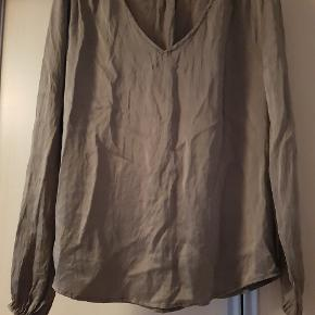 Flot grøn silke bluse med V udskæring og perler på skulderne, kan åbne og lukkes med en knap ved håndleddet.  Passes af str. S - M - L.