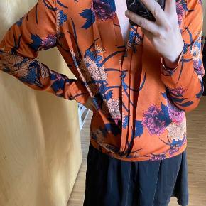 Smuk orange satinbluse med blomsterprint, fra neo noir  Med slå-om effekt, med en lille trykknap  Fremstår som ny, da den brugt højst 2 gange   #Secondchancesummer  Passer også en small  100% polyester