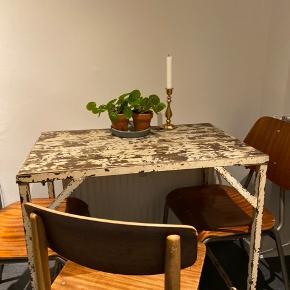 """Jeg sælger dette fine bord, selve stellet er af metal og pladen er af en slags træ, det er i super fin stand og købt """"krakeleret"""", kan både bruges som køkkenbord i et lille køkken, et lille skrivebord, en slags blomsterbord eller måske noget helt andet! Pladen er en form for planker og den ene burde blive skiftet da den har set bedre dage.  Jeg har en helt ny plade i lyst træ som evt. kan medfølge for et lille beløb. Jeg har dog ikke skiftet den selv da jeg synes bordet er så fint som det står."""