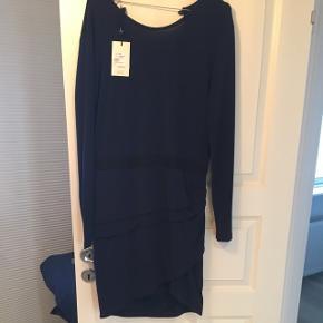 Asymmetrisk navyblå kjole fra Malene Birger. Dyb rygudskæring.  Fastsyet taljebånd og draperinger i siden som giver flot talje og skjuler muffintoppen.  Går over knæet (jeg er 170cm høj)  Nypris 1500kr.  Byd!