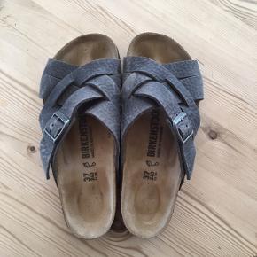 """Fede sandaler fra Birkenstock i en str 37.  Det er en ret speciel model som hedder """"Lugano"""", i farven Camberra Iron.  De er kun brugt få gange, og sælges da det var den forkerte størrelse."""