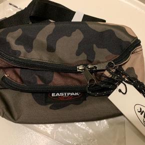 Har EN Xtra / den sidste! Camo 'Doggy' unisex bæltetaske (kan bruges som bumbag, crossbody eller mavebælte taske) fra Eastpak. 3 L og lang regulerbar rem og med flere rum. (2 foran og 1 bagpå) Bredde 27 cm Højde ca 18 cm Dybde ca 9-10 cm Sælges for 150 plus Porto