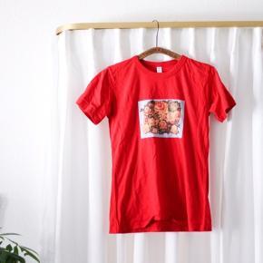 Sød T-shirt med tryk der kontrasterer t-shirtens røde stof! Trykket er i babyblå med blomster i orange nuancer.  🦋 #tuesdaysellout