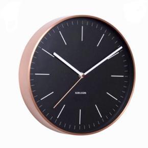 Vægur fra Karlsson med sort urskive og kobberramme. Uret er aldrig blevet brugt og sælges med original emballage. Det måler 28 cm i diameter.