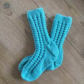 Håndstrikkede børnesokker med hulmønster i turkis garn. Foden er 16 cm.  80% uld og 20% nylon.  Prisen er fast.