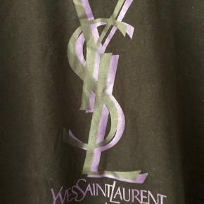 Legendarisk og ikonisk sort Yves Saint Laurent tee fra før huset blev omdøbt Saint Laurent Paris. T-shirten har fede detaljer såsom dobbeltlag af lilla materiale og 3D printet logo. Købt i butikken i London og kostede 1.900kr. Tees lignede fra huset i dag koster +2.600kr.