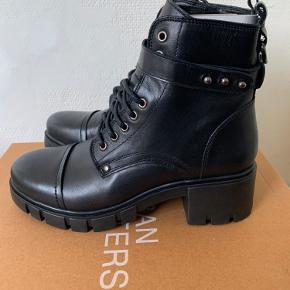 Sorte skind mili boots i str 38 ikke små i str. (Vil mene de passes af 38-38,5) Zip / lynlås i siden og lille rem med regulerbare nitte lukning. Totalhøjde ca 19 -20cm Hæl ca 5 cm (Jeg har dem selv i 37 fra efterår 19 og  Virkelig gode at have på og gå i og kan bruges hele året - virkelig blødt, Nice skind) Front sål fra 1,5 - 2,5 cm afhængig af om man måler foran eller midtpå. Sælges for langt under 1/2 pris (købt 19) Hvis afhent / mødes 340 (Har kun det ene par her tilbage)