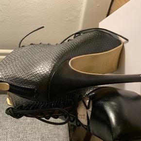 Helt nye og ubrugte stilletter i en str. 36.  Hælen er 15 cm og plateau er 5 cm.