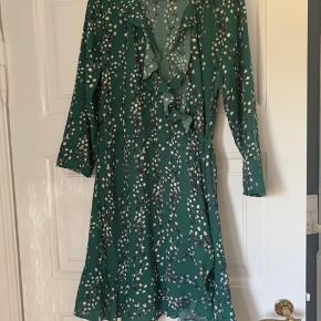 Grøn kjole dee går til knæene.