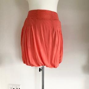 Sød ballon-nederdel fra Margit Brandt i ferskenfarvet. Der er to forlommer. Nederdelen har et bredt elastik-stykke i livet. Længde er 47 cm. Livvidde spænder fra 68 til 104 cm afhængig af, hvor meget elastikken strækkes ud. Der er ikke vaskeanvisning. Aldrig brugt – mærke sidder stadig i (dog ikke prismærke).