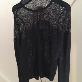 Fed bluse i let gennemsigtig strik af polyester. Lille slids i siden.  Der er et lille træk i en maske på ryggen. Det er ikke en skade eller et reelt hul.