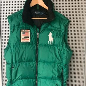 """En lækker Big pony, grøn """"Alpine puffer vest"""" med hætte, fra Ralph Lauren.  Vesten er kun brugt ganske få gange, og fremtræder derfor som næsten ny.  I lukket tilstand er den dejlig varm, og i åben kan den snildt bruges i foråret, og start sommer."""