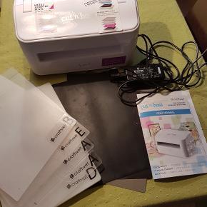 """ELEKTRISK DIECUTTER (udstansningsmaskine) til brug med dies og embossingfoldere. Nypris er ca. 1800 kr. (hertil kommer et par af pladerne, der ikke fulgte med, da jeg købte den).Maskinen er brugt men i fuldt funktionsdygtig stand. Der medfølger (selvfølgelig) strømforsyning samt følgende plader: D, 2 x A, B, E, magnetplade, metalplade og gummiplade. A-pladernes stand kan ses af billede 2 (man kan se, at de er brugt, men de er i rigtig god stand).   BEMÆRK! Jeg anbefaler, at MASKINEN AFHENTES i Tårnby (Kastrup). Alt i alt vejer den lige under 10 kg.  HVIS DEN SKAL SENDES, koster det mellem kr. 115 og 175 (med forbehold for, at jeg har læst Postnords side korrekt) - og den vil blive pakket i bobleplast og pap (original æske findes ikke længere). Du kan se videoer på Youtube om den, hvis du vil se, hvordan den virker. Den er også slået op i andre salgs""""medier""""."""