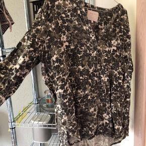 Skjorte med grønlige og brune blomster. Skjorten er lidt længere bagpå end foran og så har den knapper foran også🌸