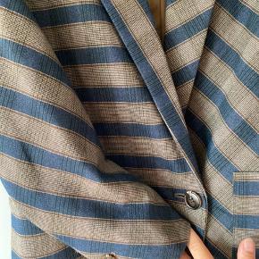 Smuk blazer fra Karen by Simonsens One kollektion. Stylenavn PageKB Boyfriend Check Blazer. Oversize herre look.  Brunt satin for. Striber og tern i forskellige retninger. Enkelt knap foran og to forskellige lommer.